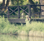 Little fisher girl holding a rod Stock Photo
