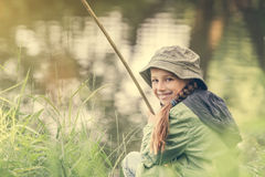 Little fisher girl smiling. Little fisher girl smiles sitting near a river with a rod stock photos