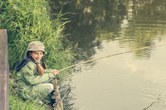 Little fisher on a river bank Stock Photos