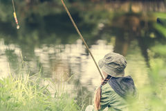 Little fisher sitting near a river Stock Photography