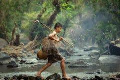 The Little fisherman boy walking in the creek royalty free stock image