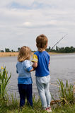 Little fishermen. Little boy and girl fishing on the lake Royalty Free Stock Image