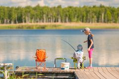Little fishermen girl and boy while fishing. On a wooden pier Royalty Free Stock Photo
