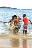 Little fishermen team with net trying caught fish