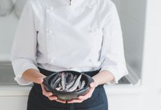 Little fishes in ceramic bowl over chef`s hands. Fresh little fishes in black ceramic bowl over chef`s hands Royalty Free Stock Image