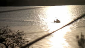 Little fishing boat through dawning sun reflection stock video