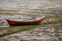 Little fishing boat stranded on the wet sand Stock Photography