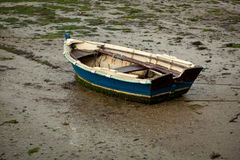Little fishing boat stranded on the wet sand. By low tide stock photo