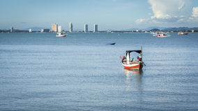 Little fishing boat on the water on the beach with blue sky and city in the background Royalty Free Stock Photography