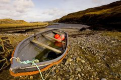 Enjoying the sun and beach after a cold voyage. The little fishing harbour at Skullomie near Tongue in the Highlands of Scotland. Fishermen use this type of royalty free stock image