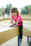Little fit girl plays on playground Royalty Free Stock Image