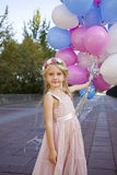 Little five-year girl in a pink dress holding balloons Royalty Free Stock Images
