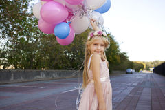 Little five-year girl in a pink dress holding balloons Stock Photo