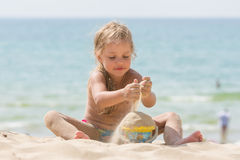 Little five-year girl pours sand into bucket baby on sea beach Royalty Free Stock Image