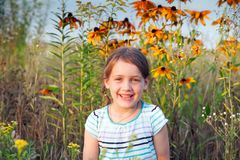 Girl walking on summer meadow. Little five year old girl in   summer field with flowers stock photography
