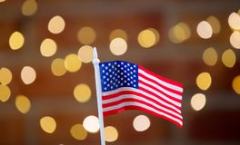 Little flag of the United States of America. On background with fairy lights and gifts in bokeh. Christmas Holiday season stock photography