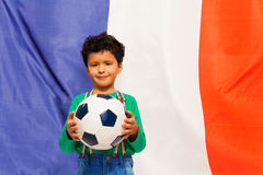 Little football fan with ball against French flag Royalty Free Stock Photo