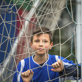 Little football player behind the football goal. Sport. Royalty Free Stock Image