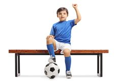 Little footballer sitting on a bench and gesturing happiness. Isolated on white background Stock Photo