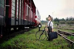 A little four years old sad boy waiting for the train. Four-year-old sad boy, dressed in retro style, stands at the train station with suitcase and old bike,he Royalty Free Stock Photo