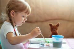 Little four years old caucasian girl coloring image by paint sitting at the table, child development stock photography