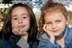 Little friends. Cute little girls daydreaming outdoors Royalty Free Stock Photography