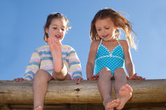 Little friends. Two little girls sitting against blue sky stock image