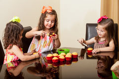 Little friends baking cupcakes Stock Photography