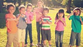 Little friends blowing bubbles in park stock video