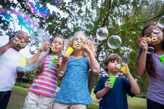 Little friends blowing bubbles in park Stock Photo
