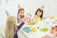 Little friends congratulating birthday girl stock images