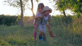 Little friends doing piggyback, boy and girl together play in countryside