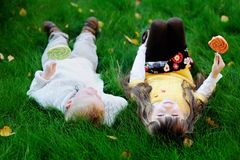 Little friends eating lollipops together on a lawn Stock Image