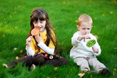 Little friends eating lollipops together on a lawn Royalty Free Stock Photography