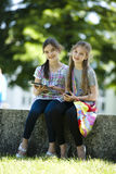 Little friends with PC tablet and mobile phone. Sitting in a garden Stock Photography