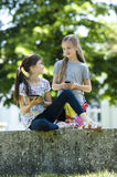 Little friends with PC tablet and mobile phone. Two little girls using PC tablet and mobile phone while sitting outside Stock Photo