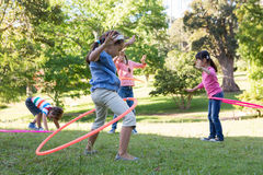 Little friends playing with hula hoops in park Royalty Free Stock Photography