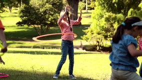 Little friends playing with hula hoops in park stock footage