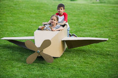 Little friends playing with toy plane on green lawn in park Royalty Free Stock Images
