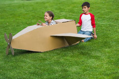 Little friends playing with toy plane on green lawn in park Stock Images