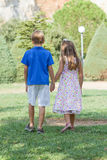 Little friends walk holding hands Stock Photo