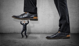 Little frightened worker under feet of huge businessman on grey wall background stock image