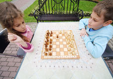 Little frowning girl and smiling boy play chess at table in park. Focus on chess royalty free stock image