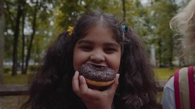 Little funny Afro-American schoolgirl eating chocolate donut with happy emotion at park. Little funny schoolgirl eating chocolate donut with happy emotion at stock video footage