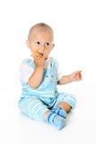Little funny baby boy holds and eats cookies Royalty Free Stock Photo