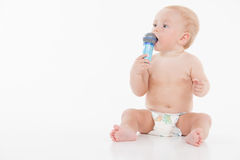 Little funny baby holding microphone and looking at copy space. Stock Images