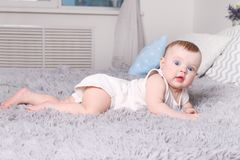 Little funny baby in white lies on bed with pillows Stock Images