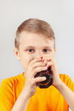 Little funny blonde boy drinking fresh cola Royalty Free Stock Photos