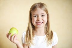 Little funny blonde girl with green apple. Portreit of little funny blonde girl with green apple Stock Photo