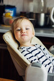 Little funny blonde infant smiling sitting in a nursing chair, looking at you stock images